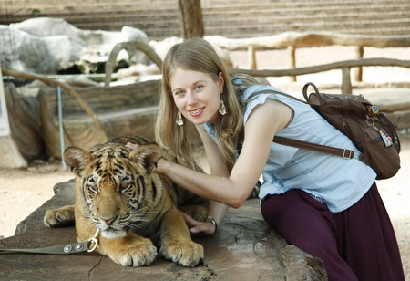 Young Caucasian girl with tiger in Thailand photo