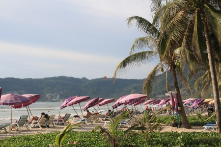 People rest at the tropical beach Patong at Phuket in Thailand - 09.08.2011