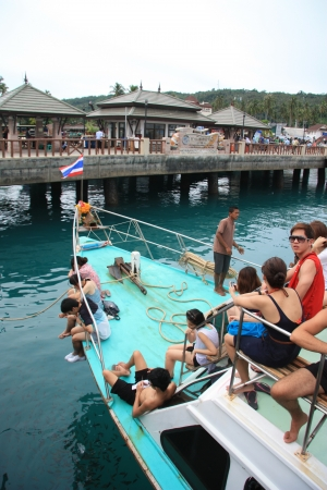 Tourists on board of a boat at the quay of Phi Phi Island watching fish in a clear turquoise water, Thailand - 11.08.2011