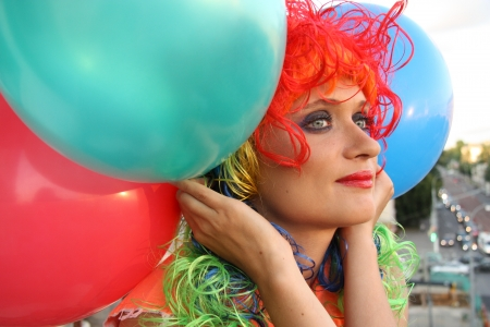 periwig: Beautiful Girl in colorful wig with balloons dreaming looking over the city