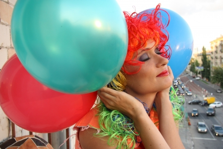 periwig: Beautiful dreaming girl with closed eyes in multicolor wig and balloons dreaming looking over the city Stock Photo