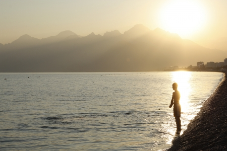 Young man in rays of the setting sun ready to enter the water, Mediterranean Sea, Konyaalti beach, Antalya, Turkey