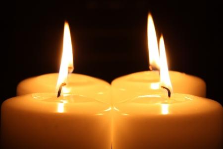 alight: Quattro candele accese in un buio Archivio Fotografico