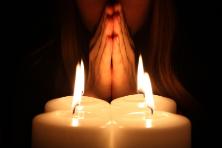 Woman prays over four alight candles in a darkness