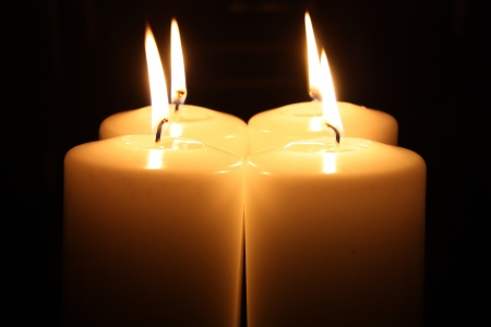 Four big candles alight in a darkness photo