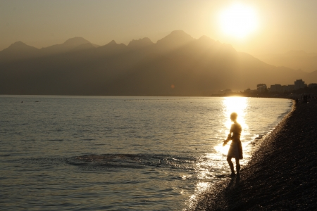 pebblestone: Young swimmer in rays of the setting sun ready to enter the water, Mediterranean Sea, Konyaalti beach, Antalya, Turkey