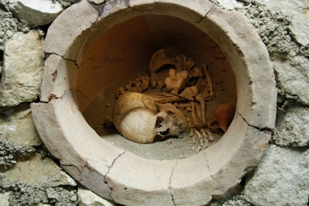 catacomb: Ancient human skull and bones in ancient burial jar in Historical Museum in Antalya, Turkey