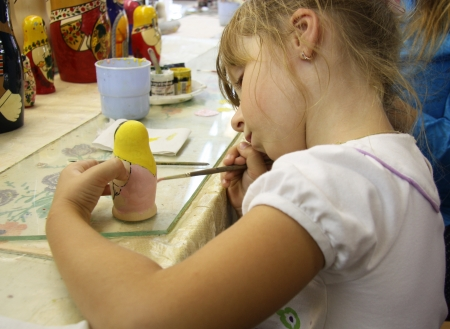 matrioshka: Little girl has a class of painting of matrioshka russian doll, Russia Stock Photo