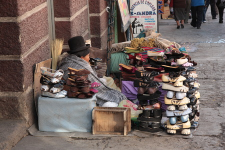 poorness: Indian Aymara woman sells traditional cholita style shoes in a street of La Paz, Bolivia, South America - 12.08.2013