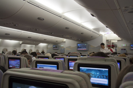 Airplane cabin interior with passengers and flight attendants - 27.07.2014