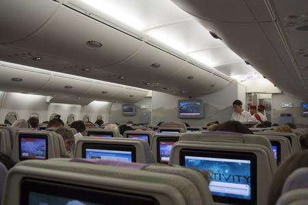 flight crew: Airplane cabin interior with passengers and flight attendants - 27.07.2014
