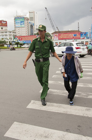 Young police man helps an old lady to cross the road, Ho Chi Minh City, Vietnam - 29.07.2014