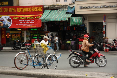 Trishaw and motorbikes in Ho Chi Minh City, Vietnam - 29.07.2014