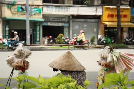 traditional goods: Vietnam street scene with a trader in a traditional vietnamese straw hat with goods, Ho Chi Minh City, Vietnam - 29.07.2014