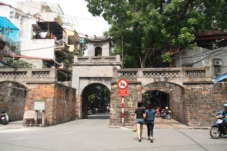 Young vietnam women walk through ancient Quan Chuong Gate in Hanoi, Vietnam - 08.08.2014