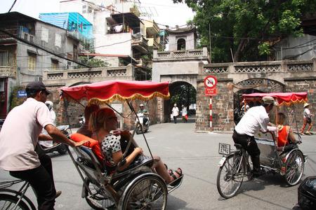 trishaw: Rickshaws make tour for tourists in old town of Hanoi, Vietnam - 08.08.2014