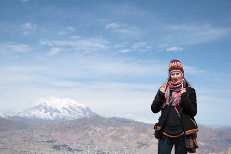 Beautiful girl traveler with panorama of Andes and La Paz city of Bolivia behind, South America photo
