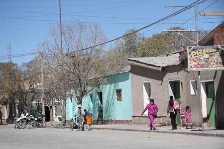 salar: Local people walk in a street of Uyuni. Uyuni is a small town near famous Salar de Uyuni Reserve, Potosi region, Bolivia, South America - 17.09.2013 Editorial