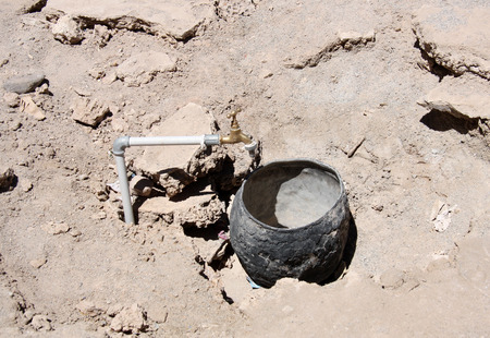 Water tap and empty pot in the Desert photo