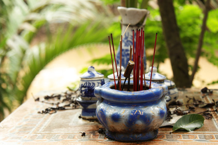 Buddhist altar with joss sticks in a tropical village photo