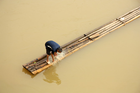 raft: Fisherman with a net at the bamboo raft in Vietnam