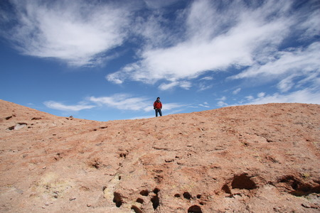 explores: Tourist man explores Ollague Volcano in Eduardo Avaroa National Park, Uyuni, Bolivia Stock Photo