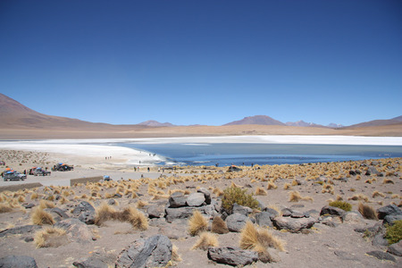 rout: Atacama Desert stone landscape and tourist cars at the lagoon in Uyuni, Bolivia, Andes