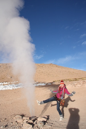Young woman tourist at the Geyser in the natural reserve Reserva de Fauna Andina Eduardo Avaroa in Bolivia