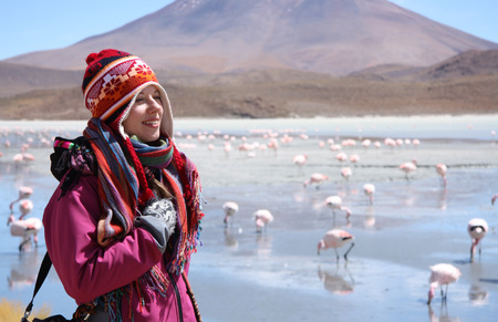 Happy young woman travels in wild nature of Andes. Laguna Hedionda with flamingos feeding in Bolivia, South America photo