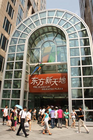 attendee: CHINA, BEIJING, 20 JULY 2010 - People are walking in front of the Malls at Oriental Plaza in the Famous Wangfujing shopping street in Beijing