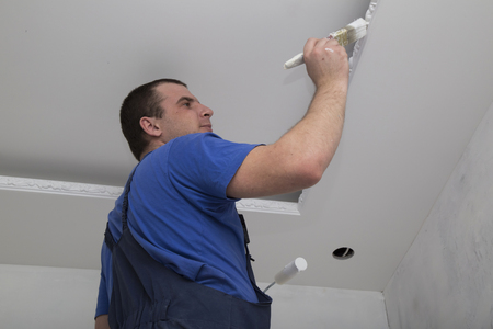gypsum: Renovation of house interior. Man worker painting the ceiling holding roller and brush with paint Stock Photo
