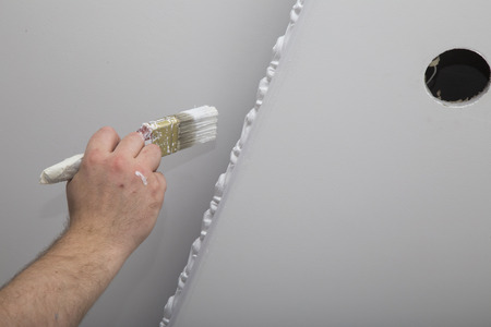 Renovation of house interior. Painting the ceiling with a brush with paint