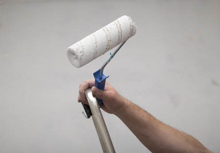 wall paint: House Renovation. Master with paint roller on the ladder repairing room interior