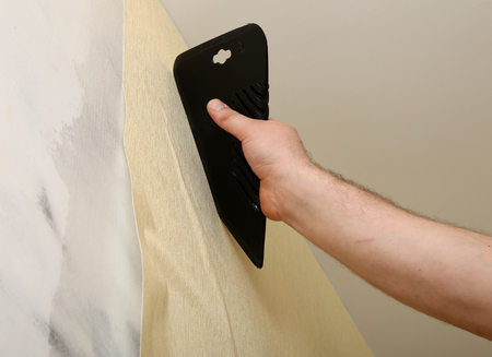 reconstruct: Worker putting up wallpaper with spatula in his hand