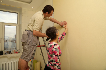 putting up: Woman customer examines the master putting up wallpaper