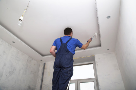 ceiling construction: Man worker paints the ceiling inside of the room interior