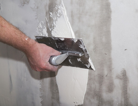 Builders float in hand applying putty on the wall