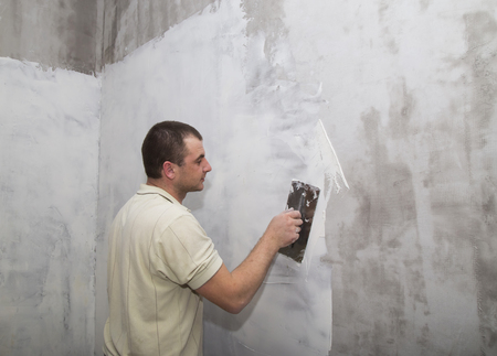 Man worker applying first layer of putty for wall with trowel