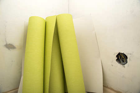 parget: Rolls of green wallpaper ready for application to wall