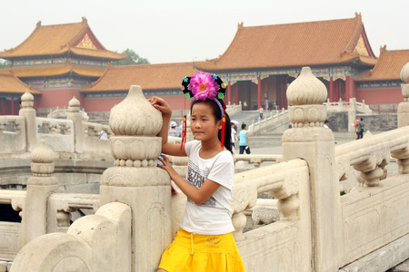 head wear: CHINA, BEIJING, 17 JULY 2010 - Chinese girl in traditional head wear is standing on the bridge across Golden Water Canal in Forbidden City in Beijing, China Editorial