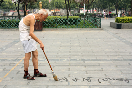 adulthood: CHINA, LUOYANG, 22 JULY 2010 - Chinese calligraphy: old man is writing Han characters on the ground with brush and water