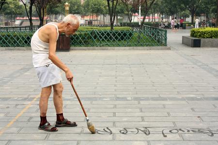 CHINA, LUOYANG, 22 JULY 2010 - Chinesische Kalligraphie: alte Mann schreibt Han-Zeichen auf dem Boden mit Wasser und Bürste