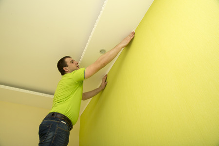 constructor: Man constructor renovates room interior with a plastic molding