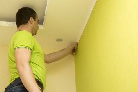reconstruct: Constructor installing white plastic molding to decorate ceiling and wall