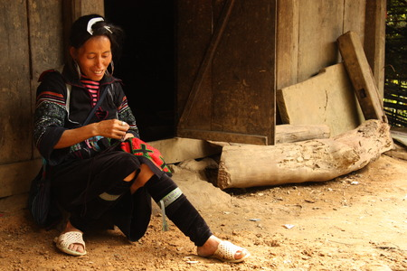 stitchwork: VIETNAM, SAPA, AUGUST 9, 2014 - Black Hmong Ethnic Minority woman sewing traditional ethnic dress in a village near Sapa, Vietnam Editorial