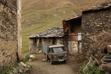 farther: GEORGIA, SVANETI, USHGULI, 9 OCTOBER 2016 - Old Soviet UAZ car in Medieval Zhibiani village of Svan people in Ushguli, Upper Svaneti, Georgia, Europe Editorial