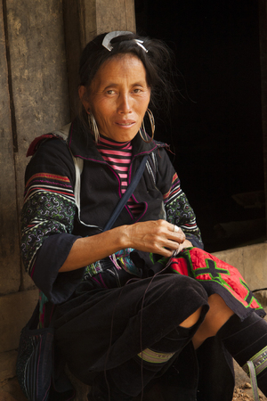 stitchwork: VIETNAM, SAPA, AUGUST 9, 2014 - Portrait of Black Hmong Ethnic Minority woman sewing traditional ethnic dress in a village near Sapa, Vietnam