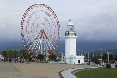 GEORGIA, BATUMI, 4 OCTOBER 2016 - View of Batumi with Ferris wheel and old lighthouse on the seafront over the cloudy sky at the Black Sea, Georgia