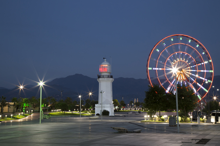 Night View of Batumi with Ferris wheel and lighthouse on the seafront over mountains, Black Sea, Georgia