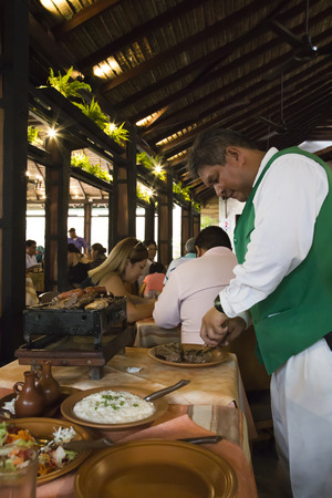 BOLIVIA, SANTA CRUZ DE LA SIERRA, 18 JANUARY 2017 - Waiter preparing food in one of the best restaurants in Santa Cruz, Bolivia